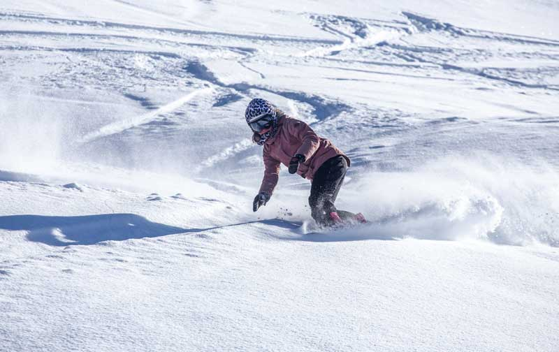 A snowboarder riders through powder at Copper Mountain